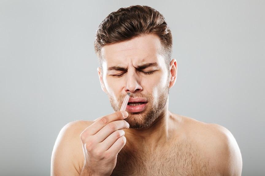 Homme douleur se retire les poils de nez à la pince à épiler